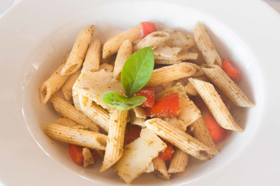 Cold pasta with pesto. Cold penne pasta served with pesto sauce, fresh tomato cubes and parmesan cheese slices