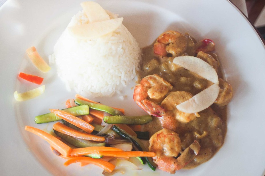 Prawn curry with apple. Prawns cooked in a yoghurt and curry sauce with apple cubes, served with basmati rice and stir fried vegetables