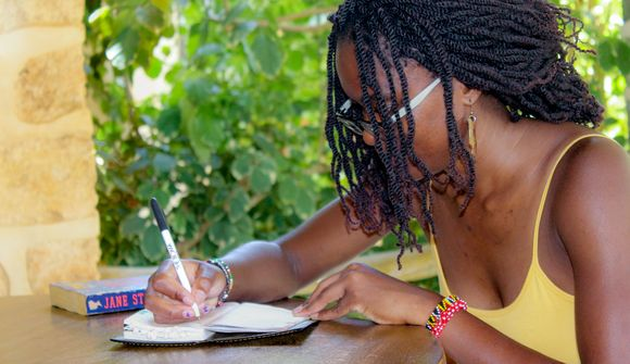 Harriet Owalla writing at a table in Lonno Lodge